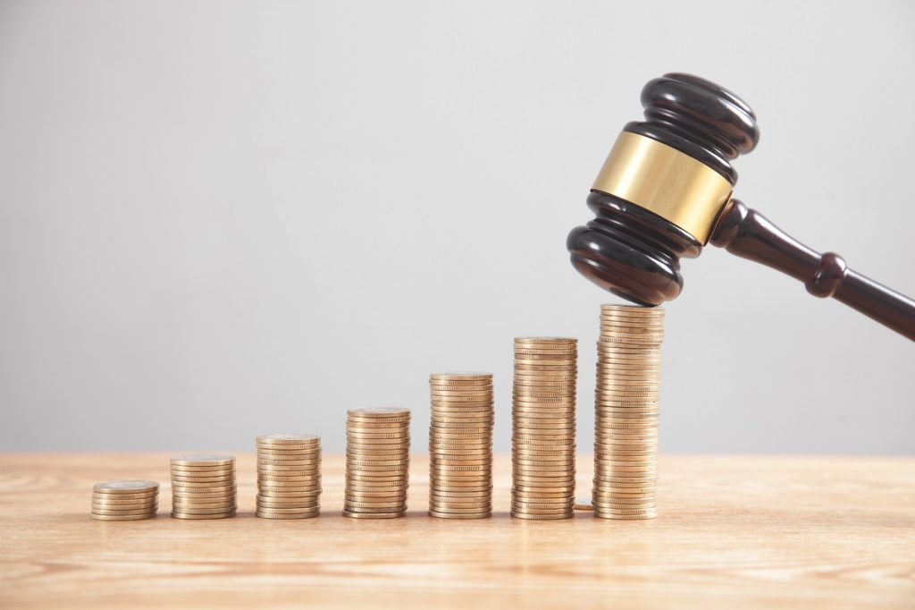 Increasing piles of money with judges gavel